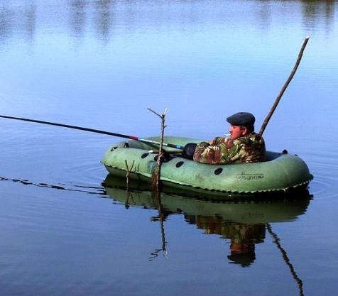 рыбак в лодке ловит карася весной